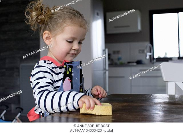 Little girl wiping table with sponge