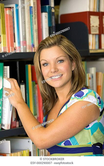 Woman in library pulling book off shelf