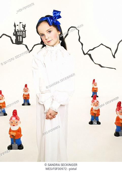 Portrait of little girl dressed up as Snow White with six dwarfs