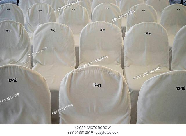 Chairs, covered with white bedspreads with numbers