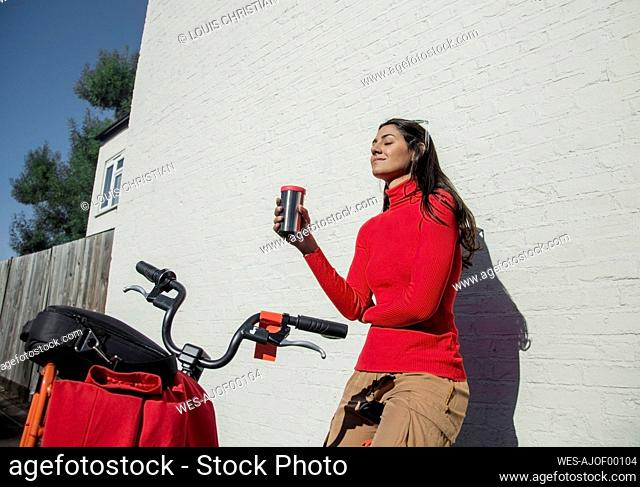 Young woman with bicycle, leaning on wall, drinking coffee from reusable cup
