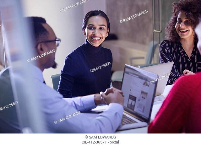 Smiling business people with laptops talking in conference room meeting