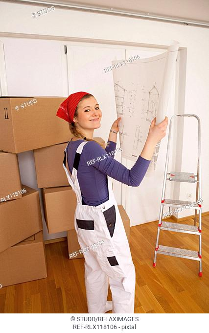 Young woman looking at blueprint layout new home