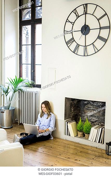 Woman sitting on the floor at home using laptop
