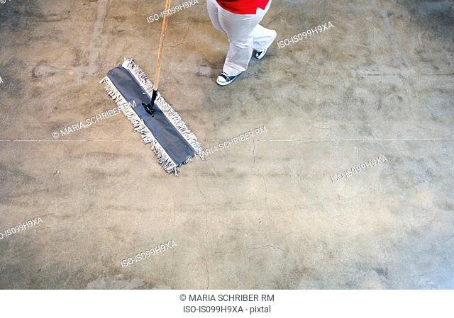 Young woman sweeping floor, low section