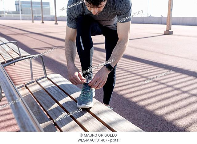 Sportive man lacing his shoes on a bench