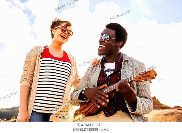 Couple singing together and playing ukulele outdoors