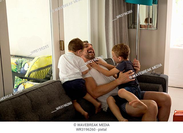 Father playing with his sons in living room