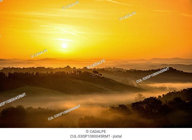Sunrise over foggy rural landscape