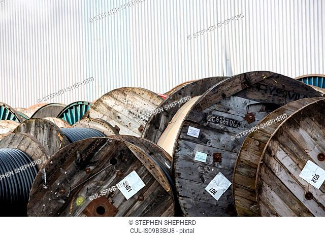 Large group of wooden cable drums in industrial yard