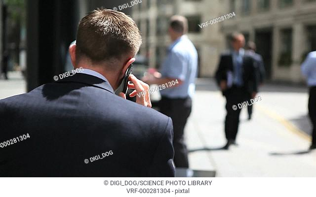 Businessman wearing a suit jacket talking on a cell phone with his back to the camera