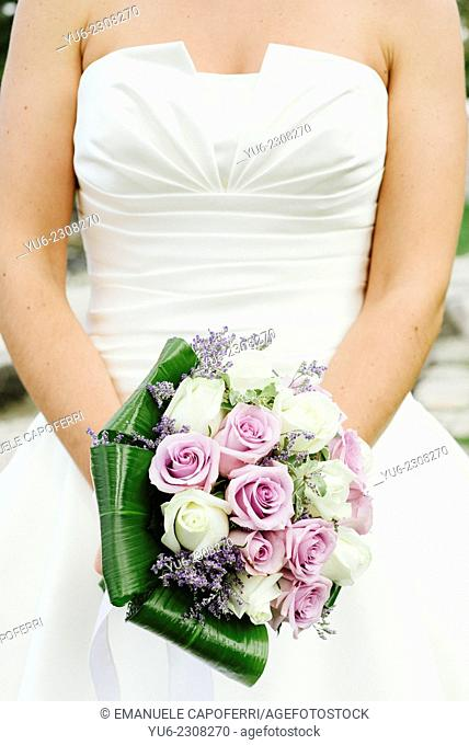 Hands of the bride with a bouquet of flowers