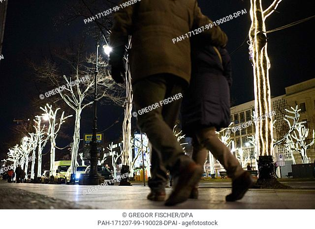 Tourists walk below illuminated trees on a pavement in Berlin, Germany, 7 December 2017. After a lack of sponsors, the traditional Christmas lights of the...