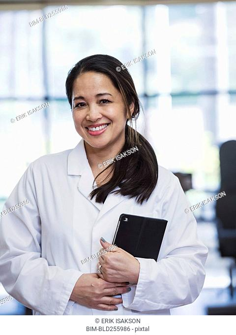 Portrait of smiling Asian physical therapist holding digital tablet