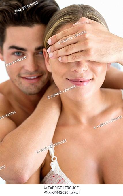 Man covering eyes of his girlfriend