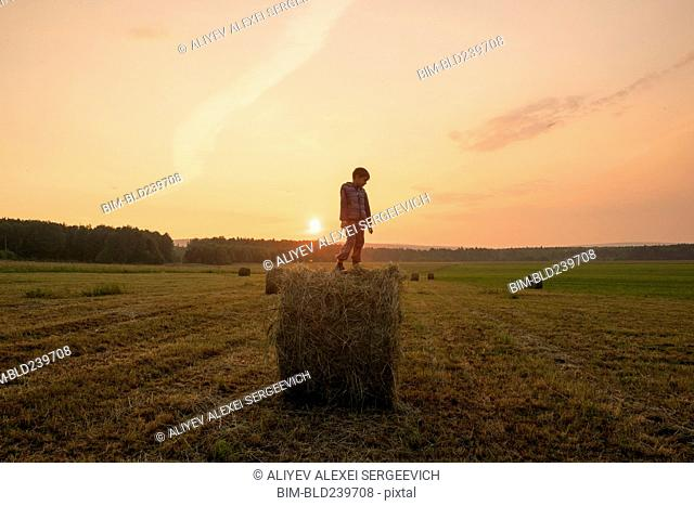 Mari boy standing on hay bale in field, Ural, Russia