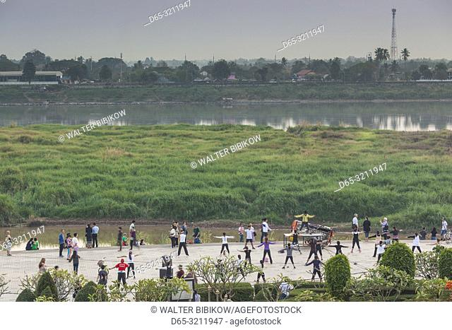 Laos, Vientiane, Mekong Riverfront, high angle view of outdoor excercise class, dusk, NR