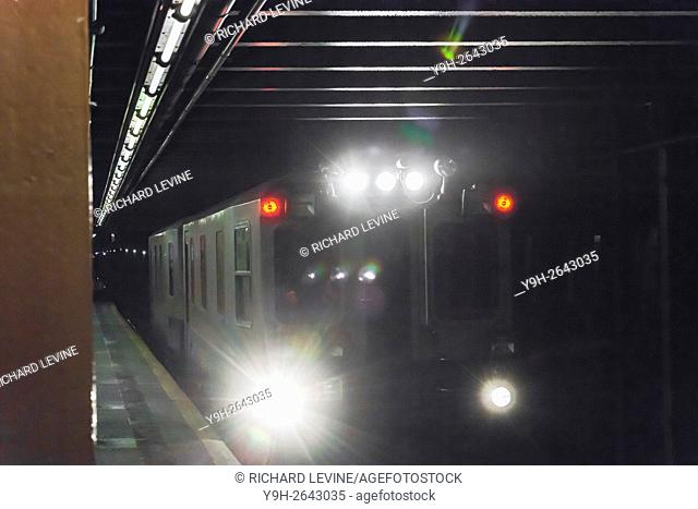 The bright lights of a NYCTA subway track inspection train are seen as the train passes through the West 23rd Street station