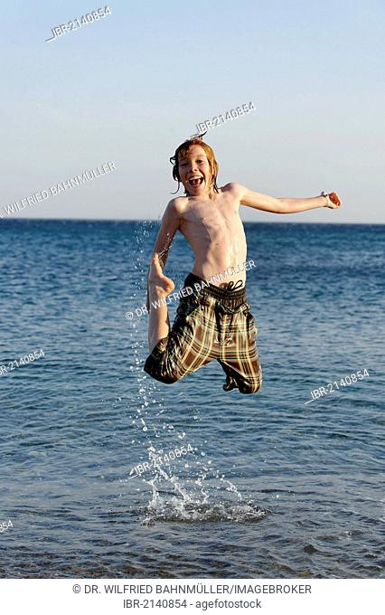 Happy boy jumping in the sea