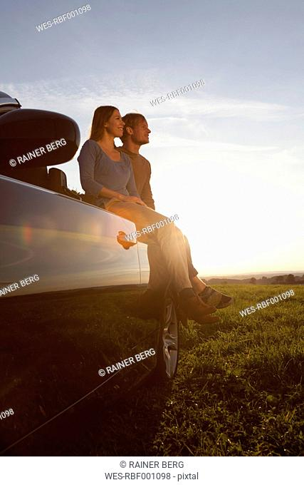 Germany, Bavaria, Couple sitting on car