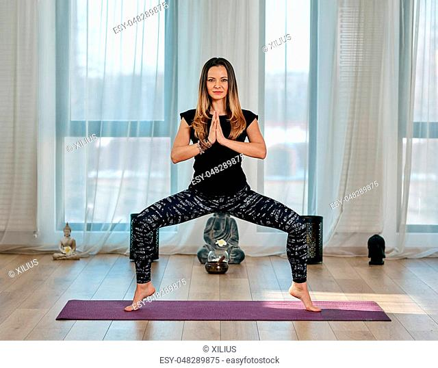 Yoga trainer in various postures (asana) in a studio