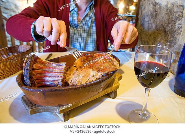 Man's hands serving roast lamb in a restaurant. Madrid, Spain