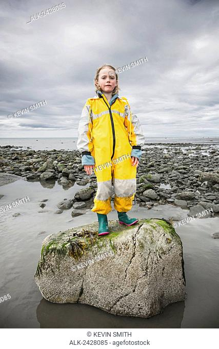 Young child wearing yellow dry suit stands on a rock at Bishop's Beach, Kachemak Bay, Homer, Southcentral Alaska, USA