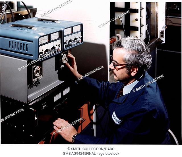 Scientist Alan Attia wearing a blue uniform and eyeglasses cycling an 8KWH bi-polar battery, 1980. Courtesy US Department of Energy. ()