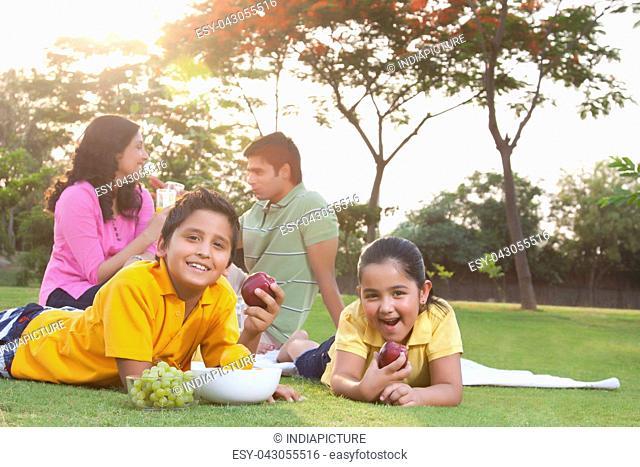 Portrait of children eating fruit