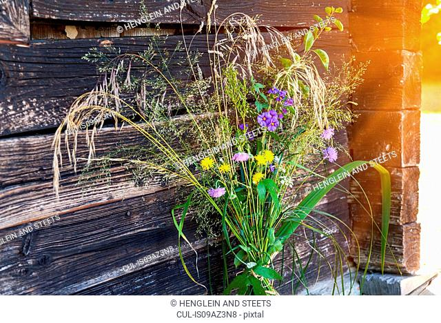 Bunch of freshly picked wildflowers in front of garden shed