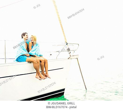Couple wrapped in towels on deck of sailboat