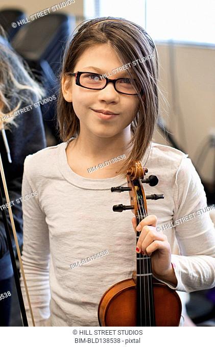 Caucasian girl holding violin in music class