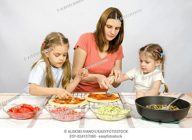 Mom helps younger daughter spread ketchup on a pizza, the eldest daughter, she is preparing a second pizza