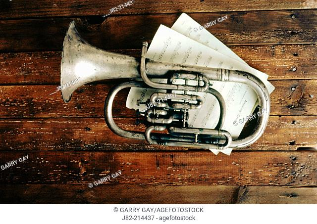 Old silver horn on wooden wall with sheet music