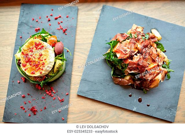 food, culinary, haute cuisine and cooking concept - goat cheese and prosciutto ham salads on stone plates at restaurant or cafe