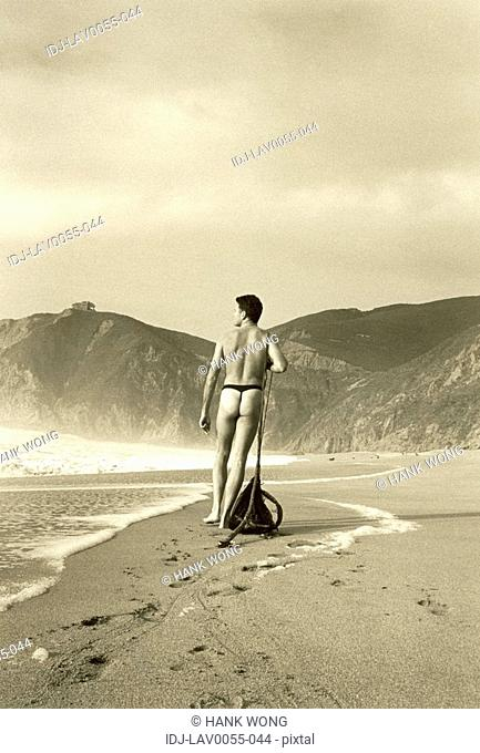 Rear view of a naked man pulling fishing net on the beach