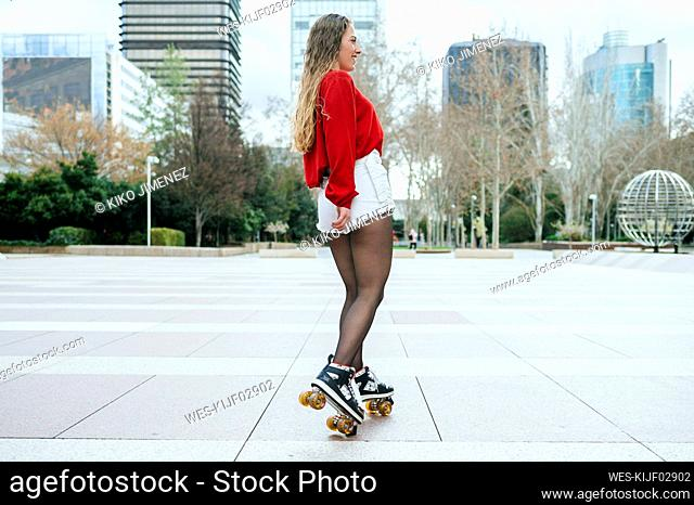 Happy young woman roller skating in the city