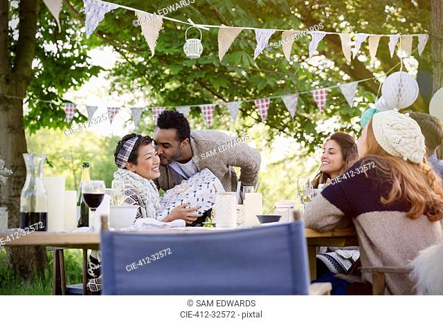 Boyfriend kissing girlfriend with birthday gift at garden party table