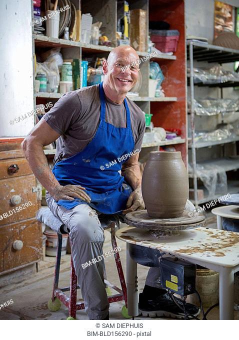 Older Caucasian man forming pottery on wheel in ceramics studio