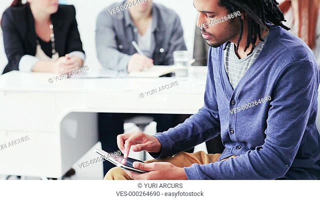 Young businessman working on a digital tablet with colleagues in the background
