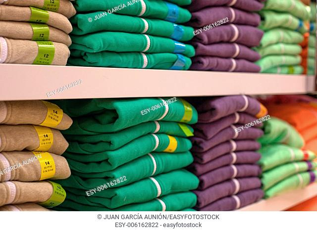 Piles of multicolored cotton clothing on the shelves of a fashion shop