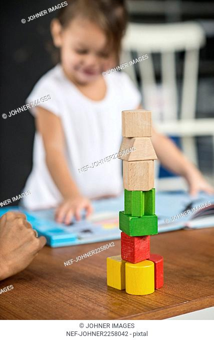 Multi-colored tower from wooden blocks, girl in background