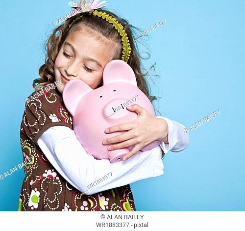 Girl (8-9) embracing piggybank, studio shot