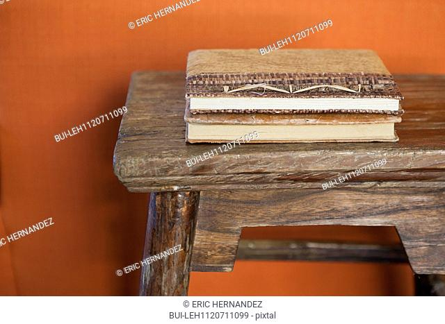 Close-up of books on a cropped wooden table against orange wall; Azusa; California; USA