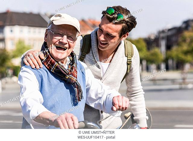 Happy senior man with adult grandson in the city on the move