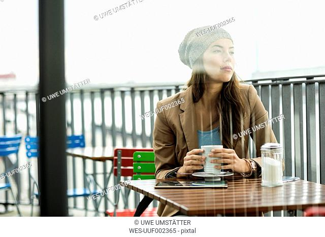 Daydreaming young woman sitting at sidewalk cafe