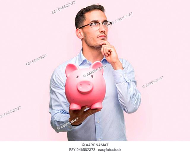Handsome young man holding a piggy bank serious face thinking about question, very confused idea