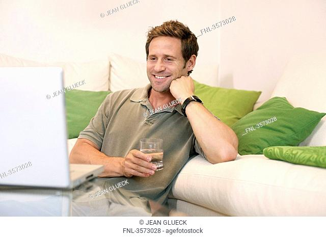 Happy man in living room looking at laptop