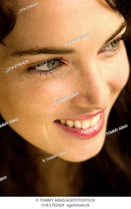 a green eyed woman smiling and looking left