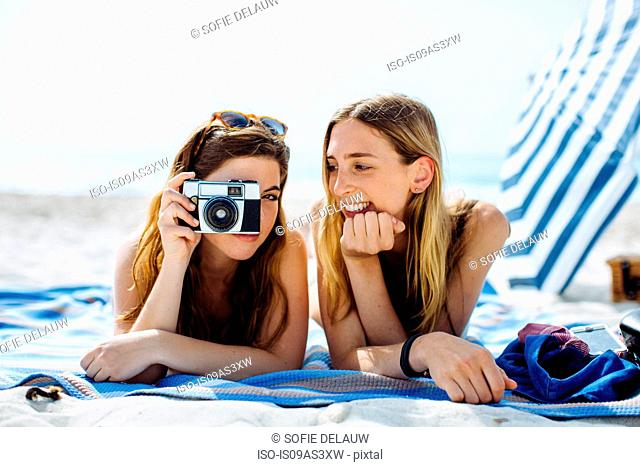 Two young female friends photographing whilst sunbathing on beach